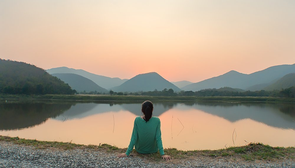 Woman having a mindful moment to enjoy the sunset over a lake